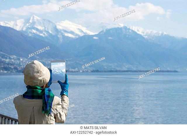 Tourist takes a photograph of the Swiss Alps and Lake Maggiore on her tablet; Brissago, Ticino, Switzerland