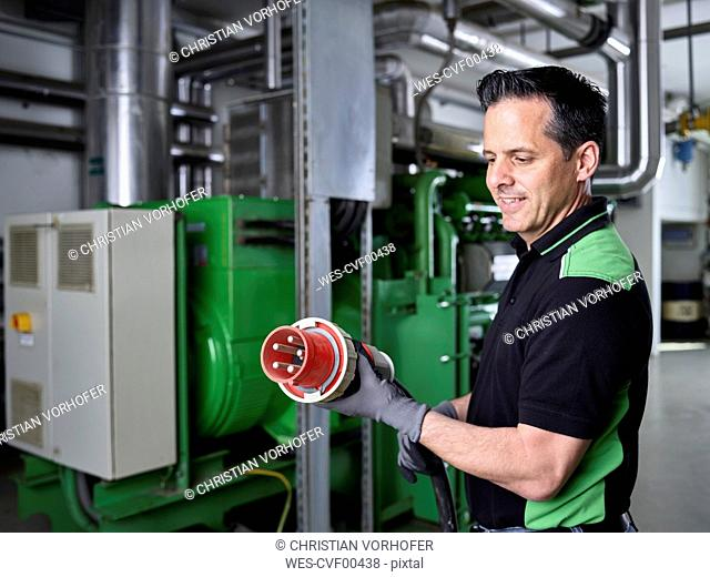 Combined heat and power plant, worker holding high current plug