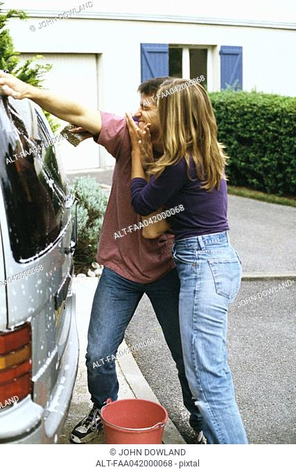 Couple washing car together, laughing