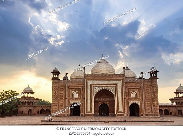 The red facade of mosque located near of Taj Mahal in back lit of summer sunset. Agra, Uttar Pradesh. India