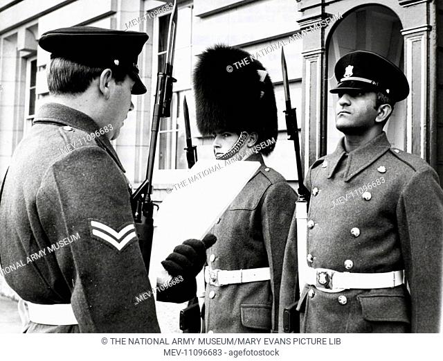 Photograph of changing the guard at Buckingham Palace, L/Cpl Hassam Judoo, 1st Bn The Devonshire and Dorset Regiment relieving a sentry of the Welsh Guards
