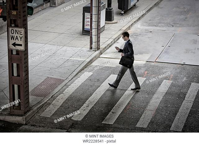 View from above of a man in the middle of a pedestrian road crossing, looking at his phone