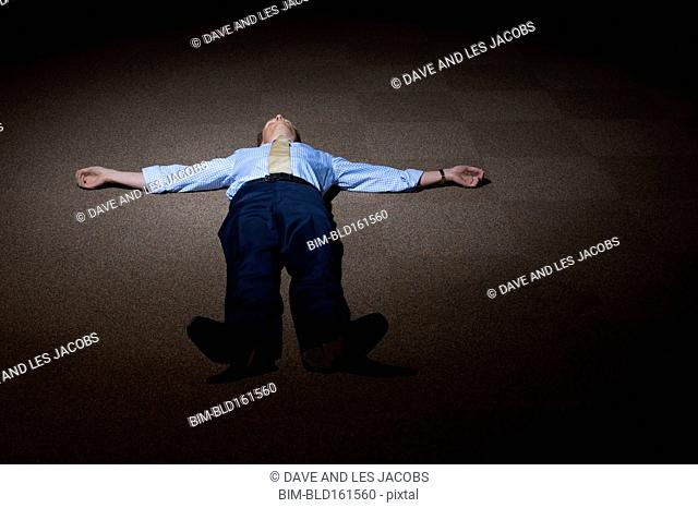 Lonely Caucasian businessman laying on floor in spotlight