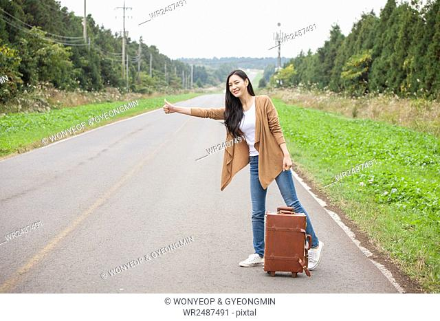 Young smiling woman standing and trying to hitch a ride with a carrier on a road