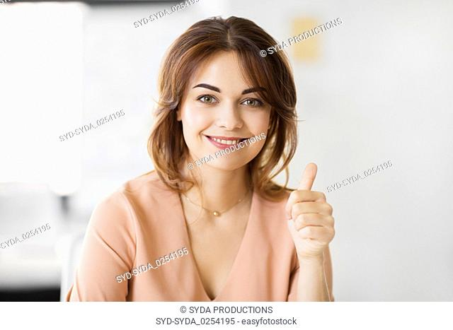 portrait of smiling young woman showing thumbs up
