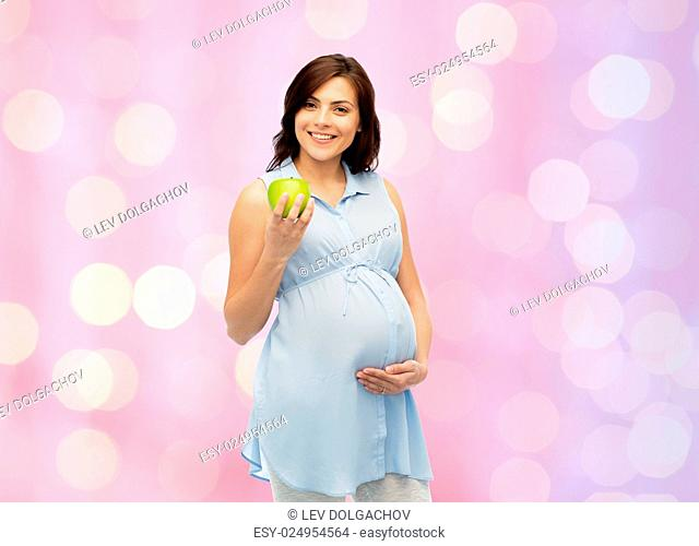 pregnancy, healthy eating, food and people concept - happy pregnant woman holding green apple over rose quartz and serenity holidays lights background