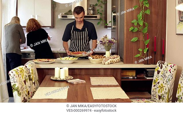A man smelling pizza and two women helping him to prepare a lunch at home