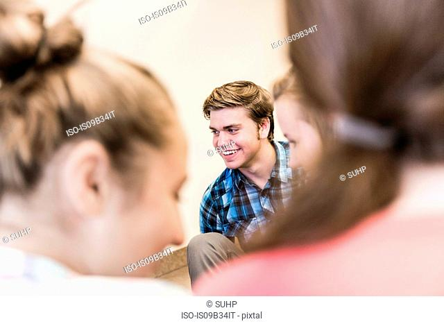 Over shoulder view of male and female high school students having classroom group discussion