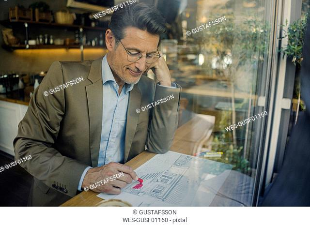 Mature businessman sitting in coffee shop, drawing outline of a house
