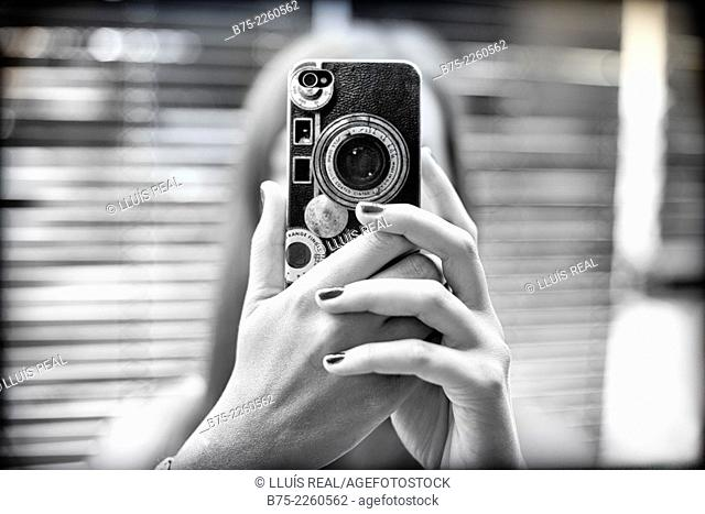 Young blond woman holding a mobile phone with hands in front of the face taking a picture