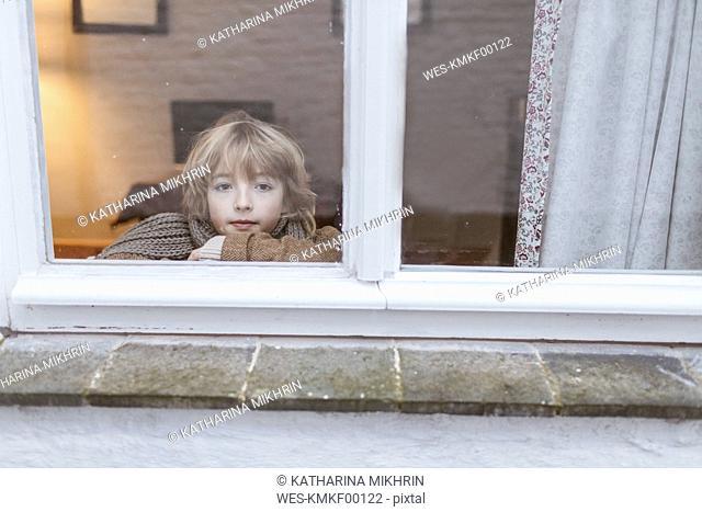 Portrait of pensive boy looking out of window