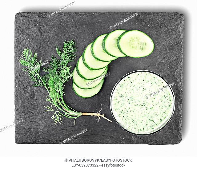 Cucumber smoothie top view. Cucumber, dill, cottage cheese whipped in a glass on a slate stone