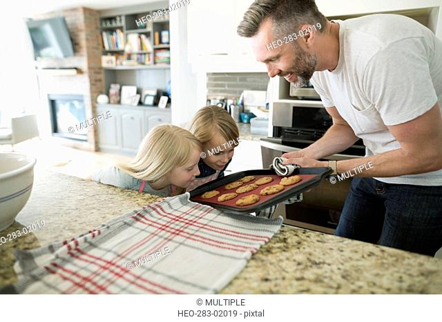 Father and daughter baking cookies in kitchen