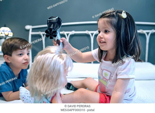 Girl blow-drying hair of doll watched by brother