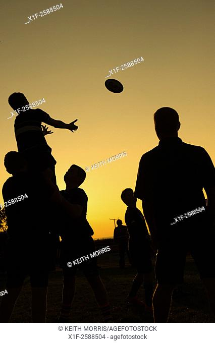 Silhouettes of young teenage men boys taking part in rugby training coaching practicing lineout ball handling, at dusk, Aberaeron Wales UK