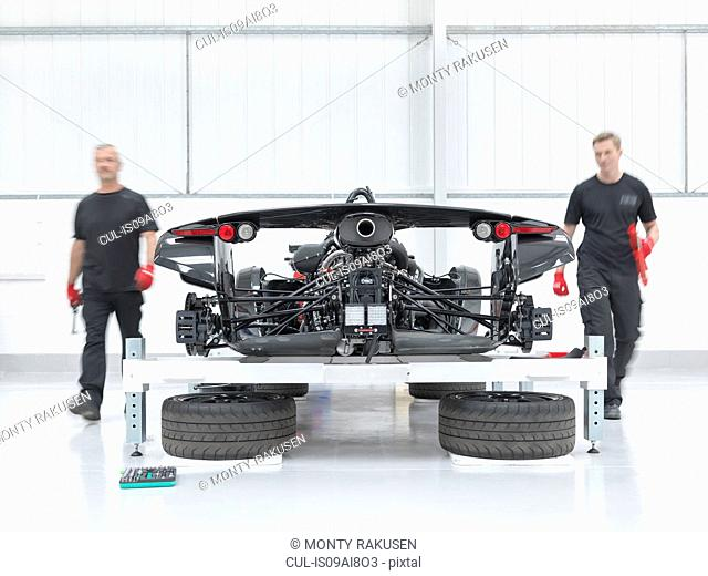 Engineers assembling supercar in sports car factory