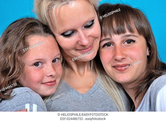 A mother smiles as she receives a kiss on the cheek from her young daughters