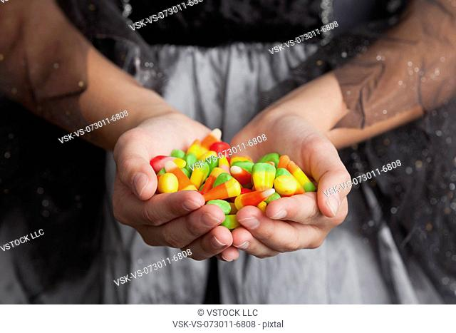 Midsection of teen girl holding handful of candies