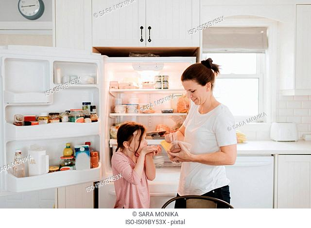 Mother giving daughter cold meat from fridge