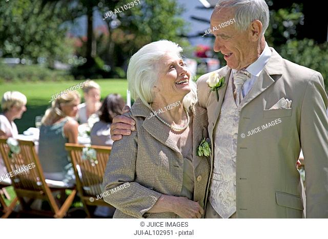 A senior couple with arms around each other at a wedding reception