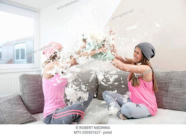 Two female friends sitting on couch at home having pillow fight