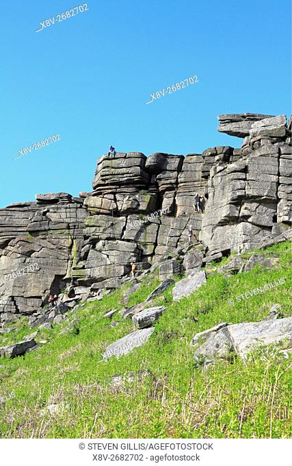 Climbers on Stanage Edge in the Peak District National Park, Derbyshire, England, UK