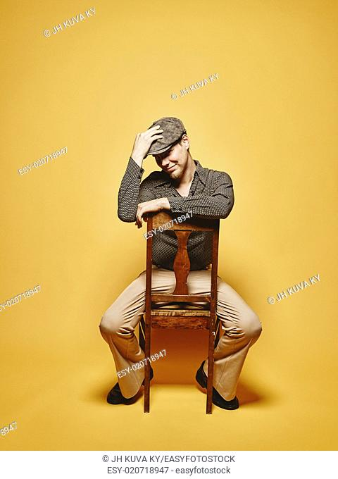 Expressive man sits on the chair and 70's look theme, yellow background
