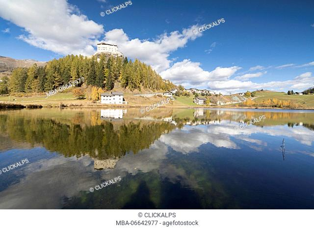 The ancient castle and colorful trees are reflected in Lake Tarasp Inn district Canton of Graubünden Engadine Switzerland Europe