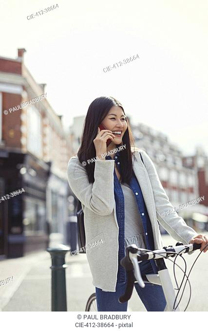 Smiling young woman commuting with bicycle, talking on cell phone on sunny urban street