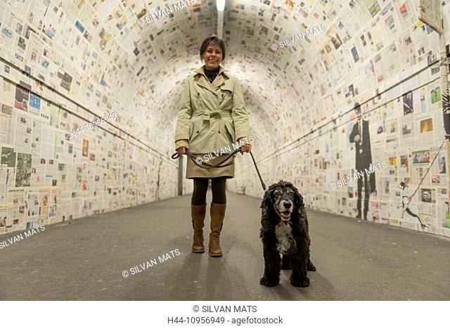 Woman walking in a tunnel with her dog and decorated with newspaper in lugano ticino Switzerland, Europe