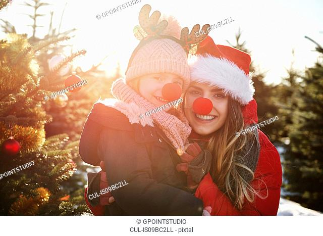 Girl and mother in christmas tree forest with red noses, portrait