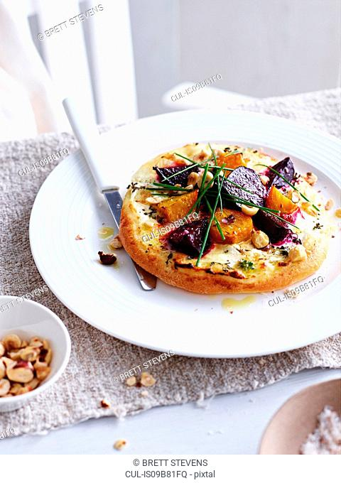 Beetroot, goats cheese and hazelnut pizza on white plate
