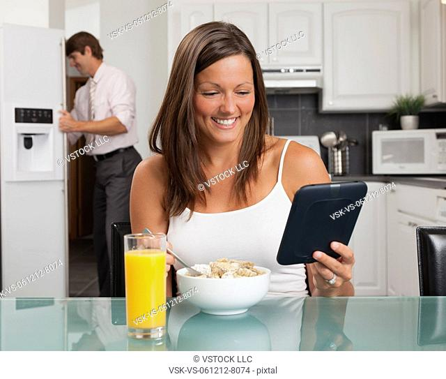 USA, Illinois, Metamora, young woman having breakfast cereal and holding digital tablet