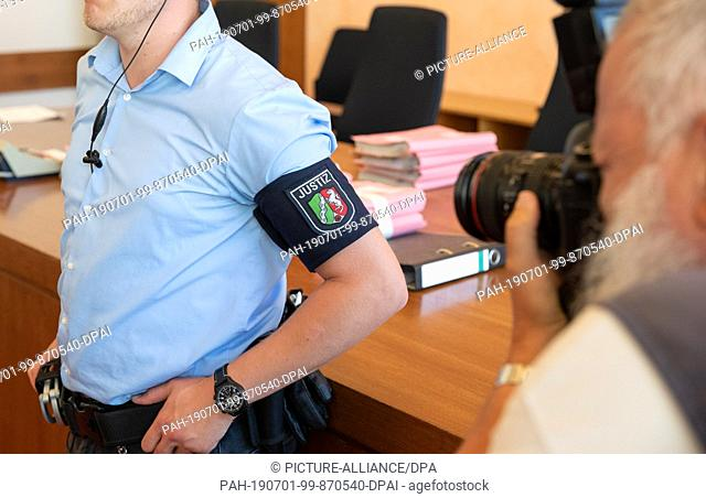 28 June 2019, North Rhine-Westphalia, Detmold: A justice official with an armband is standing in the courtroom of the Detmold Regional Court