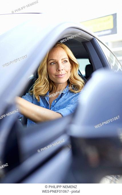 Smiling woman driving car looking out of window