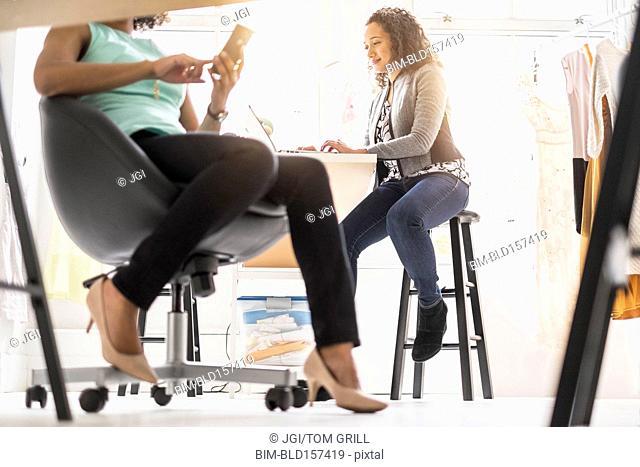 View underneath desk of businesswomen working in office