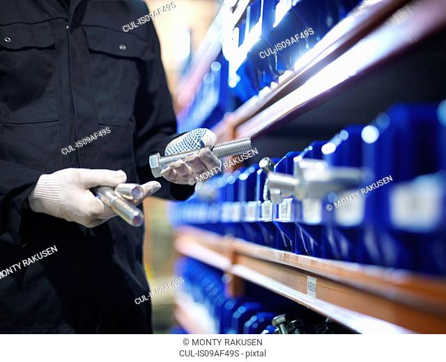 Engineer selecting bolts from store in engineering factory, close up