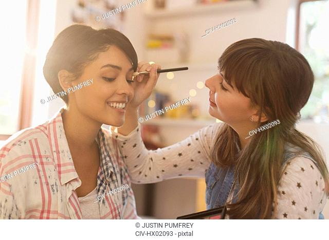 Young women friends applying makeup
