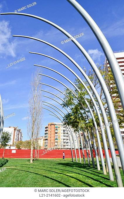 Futuristic Sculpture, green grass, red wall, buildings, blue sky. Plaça Europa, Plaza Europa, District VII, Gran Via, Hospitalet de Llobregat