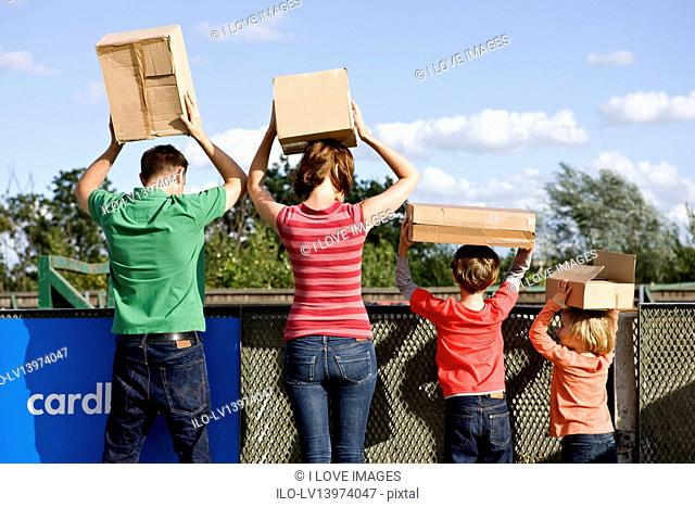A family disposing of cardboard boxes at a recycling centre, rear view