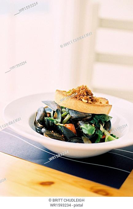 Mussels, shellfish on a white china dish. Garnishes
