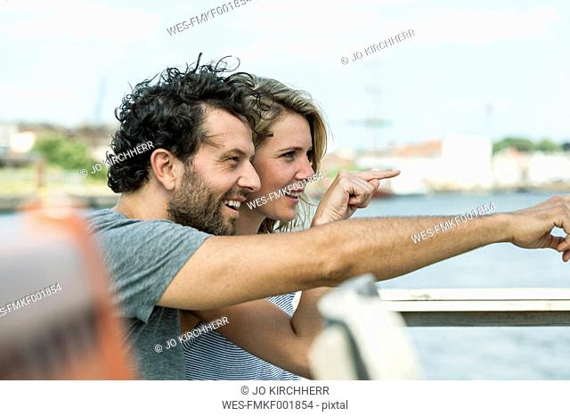 Germany, Luebeck, smiling couple pointing at something