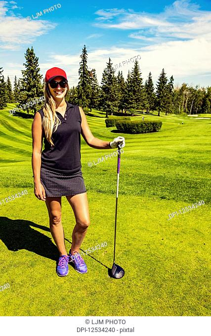 Portrait of a female golfer standing with her driver on the green grass of a golf club; Edmonton, Alberta, Canada