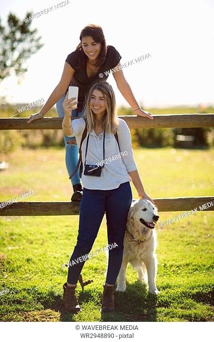Friends with dog taking selfie in farmland