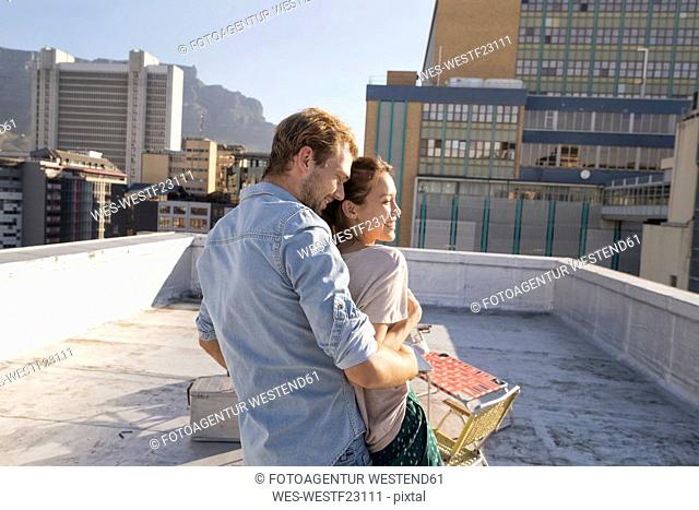 Young couple celebrating on a rooftop terrace, embracing at sunset