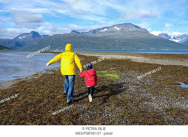 Norway, mother and daughter running at the beach, Lyngen fjord