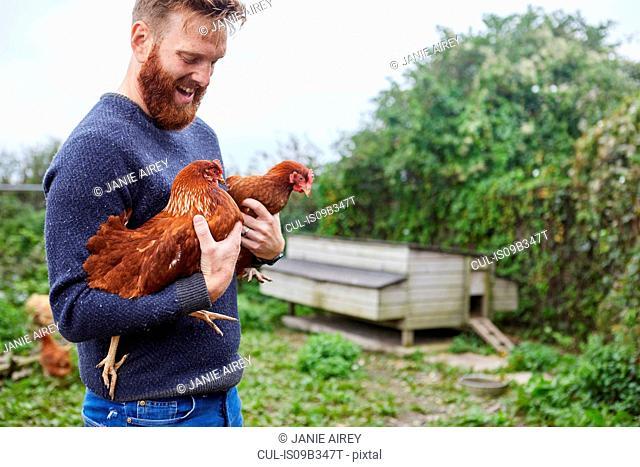 Man holding chickens