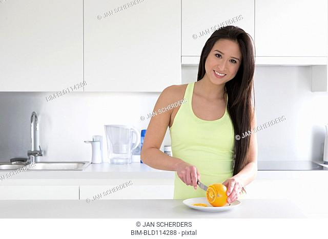 Mixed race woman slicing fruit in kitchen