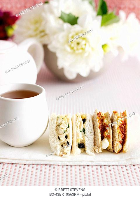 Sliced sandwiches with cup of tea