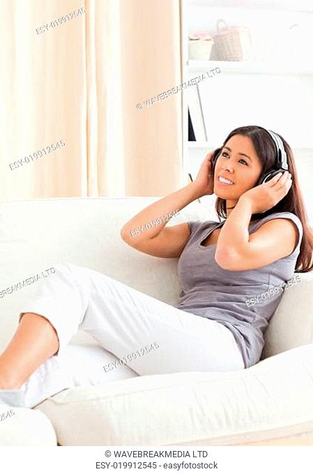 smiling woman with earphones looking up sitting on sofa